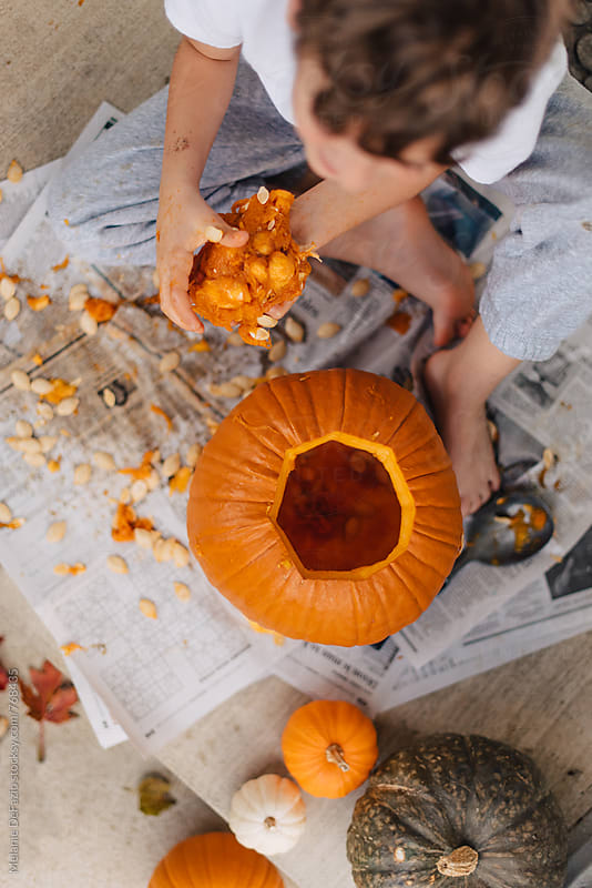 Carving pumpkins by Melanie DeFazio for Stocksy United
