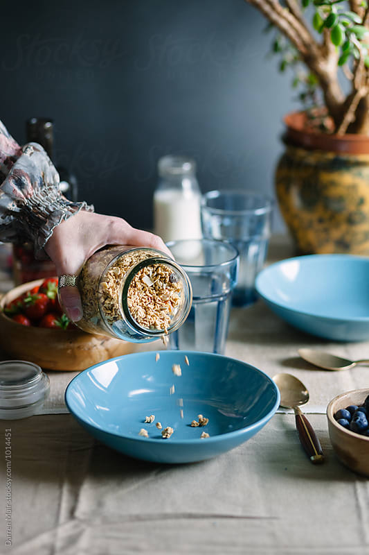 Breakfast: Woman pouring granola from a jar into a bowl. by Darren Muir for Stocksy United