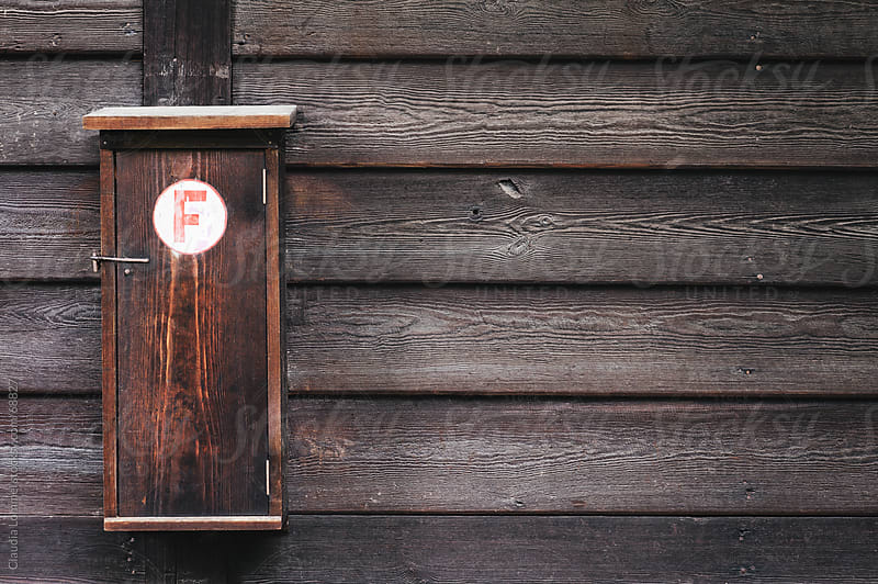 Wooden Wall of a Barn, Fire Extinguisher, Background by Claudia Lommel for Stocksy United