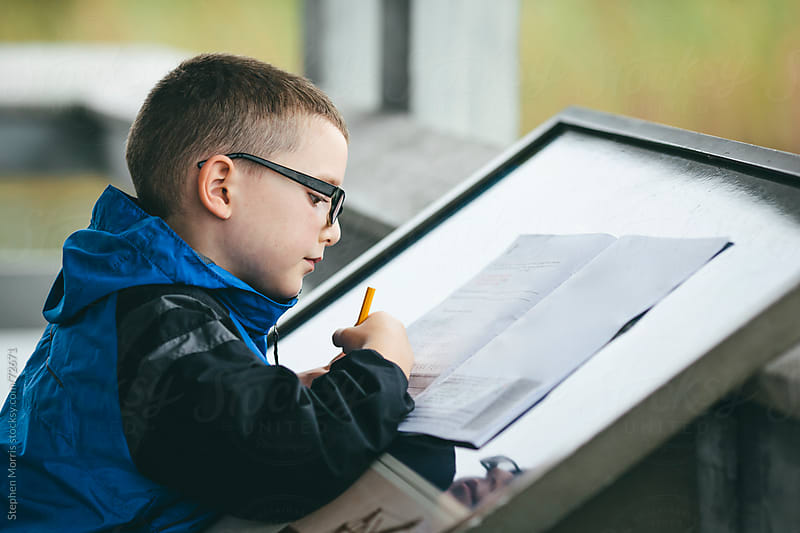 Boy Completing Workbook at National Park by Stephen Morris for Stocksy United