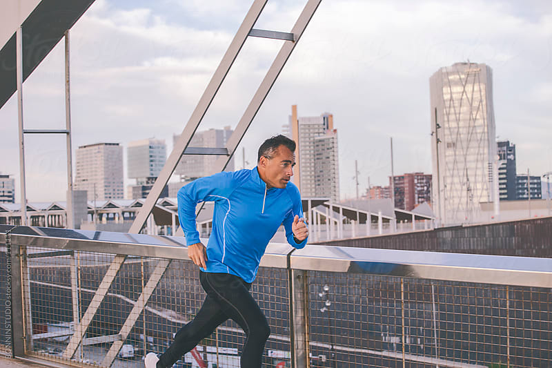 Man sprinting on a urban bridge. by BONNINSTUDIO for Stocksy United
