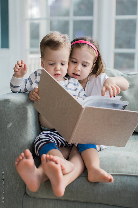 Brother and sister sitting in a big chair looking in a book by Jakob for Stocksy United