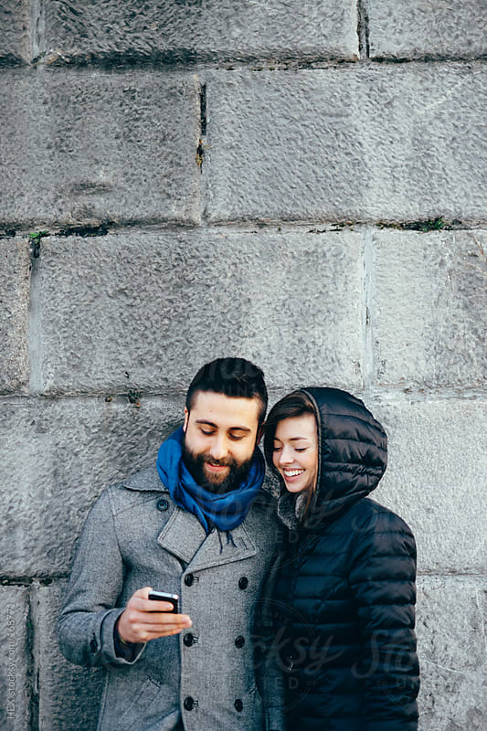 Young Couple Using Mobile Phone . Wall Background by HEX. for Stocksy United
