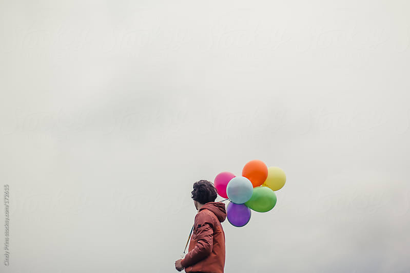 Teenage boy against a cloudy sky holding a bunch of balloons by Cindy Prins for Stocksy United