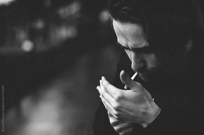 Man Lighting a Cigarette in Black and White by Briana Morrison for Stocksy United