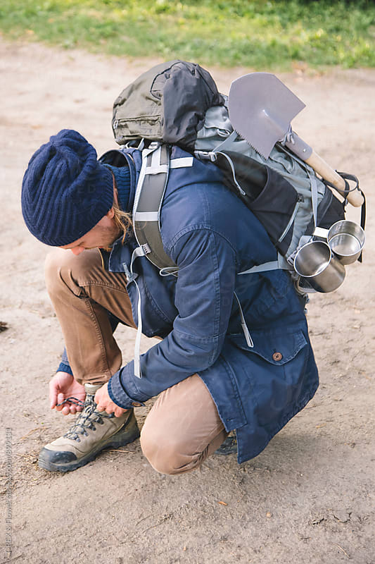 Traveller tying shoe laces by Danil Nevsky for Stocksy United