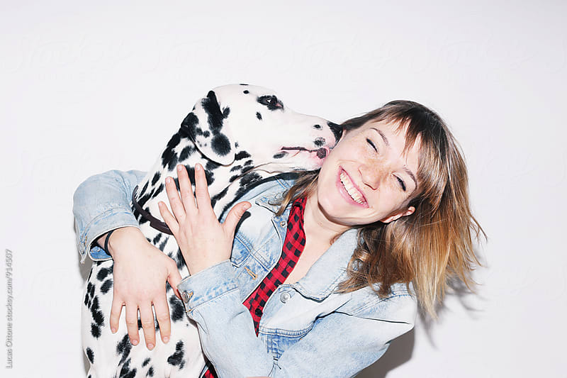 Dalmatian dog kissing a girl by Lucas Ottone for Stocksy United