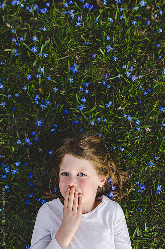 Girl lying in grass with blue flowers by Lindsay Crandall for Stocksy United
