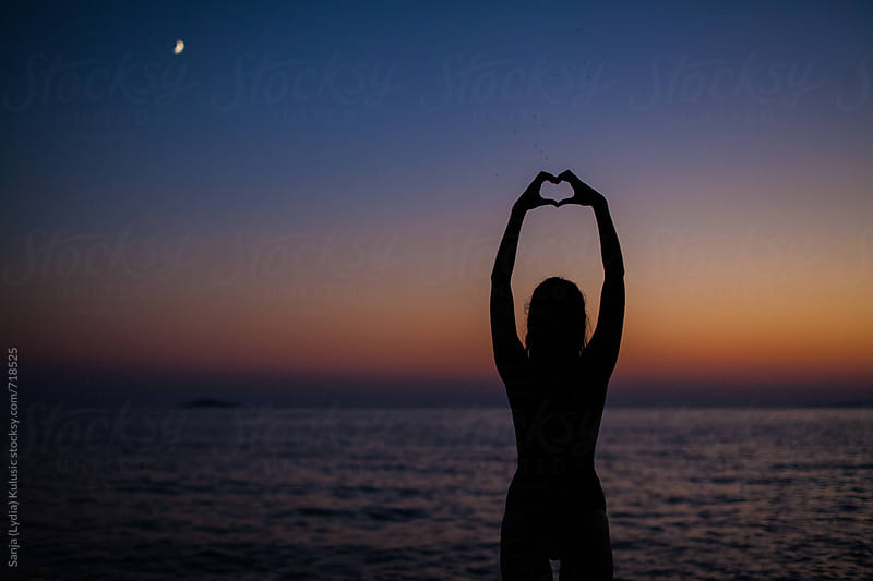 Shadow of a fit girl making a heart sign with her hands in the sunset  on the sea by Sanja (Lydia) Kulusic for Stocksy United