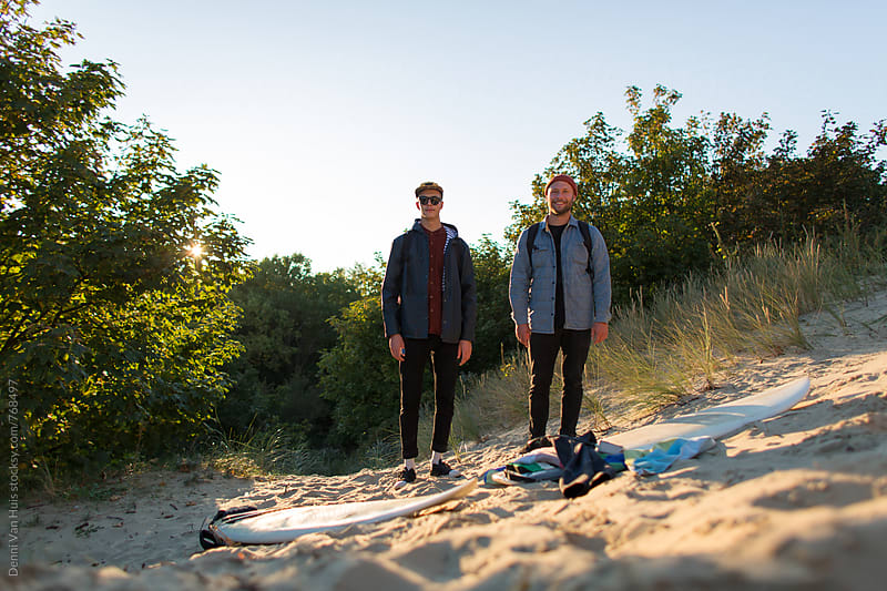 Two friends smile and pose in the dunes by Denni Van Huis for Stocksy United