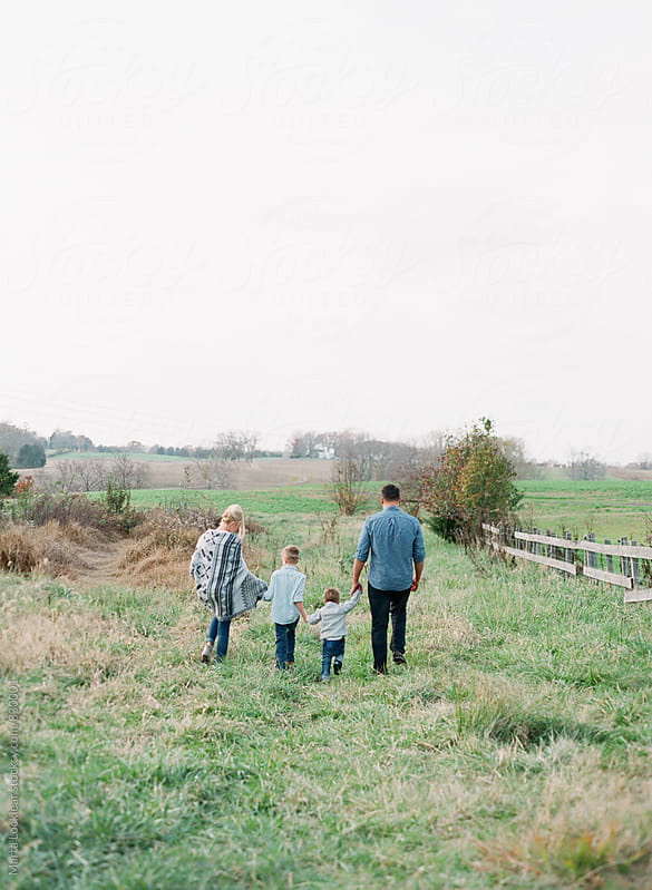 Family Walking Through a Field Together by Marta Locklear for Stocksy United
