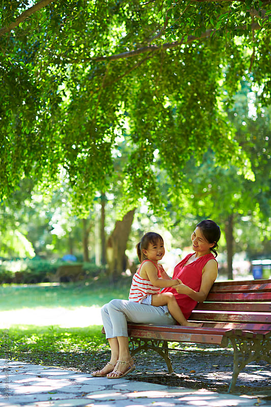 little asian girl sitting on her mother's leg in the park by Bo Bo for Stocksy United