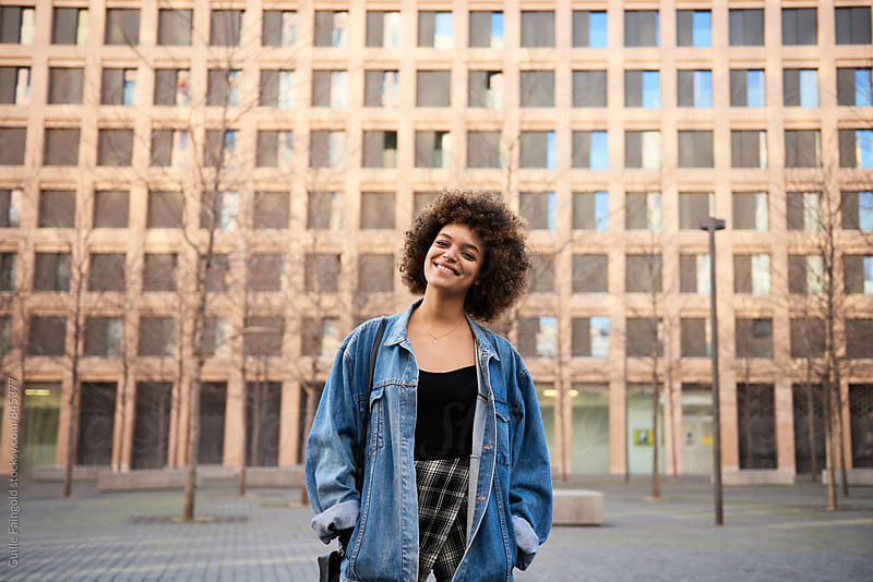 Portrait of young smiling woman with afro looking at camera by Guille Faingold for Stocksy United