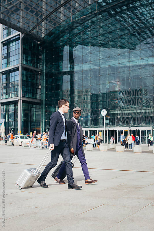 Caucasian and Black Businessman Walking Side by Side in Front of Large Modern Glass Building by VISUALSPECTRUM for Stocksy United