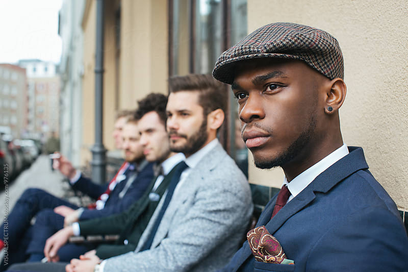 Outdoor Headshot of Handsome Young Black Man Sitting with Friends in Café by VISUALSPECTRUM for Stocksy United