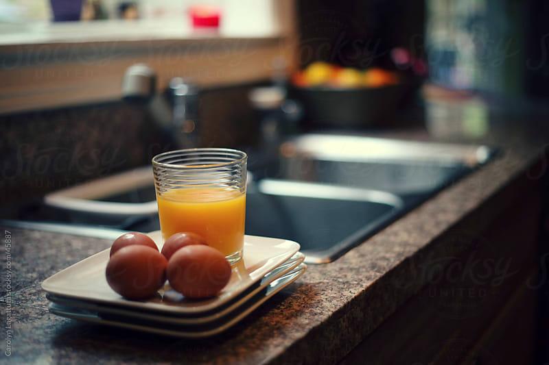 Eggs and orange juice for breakfast preparation by Carolyn Lagattuta for Stocksy United