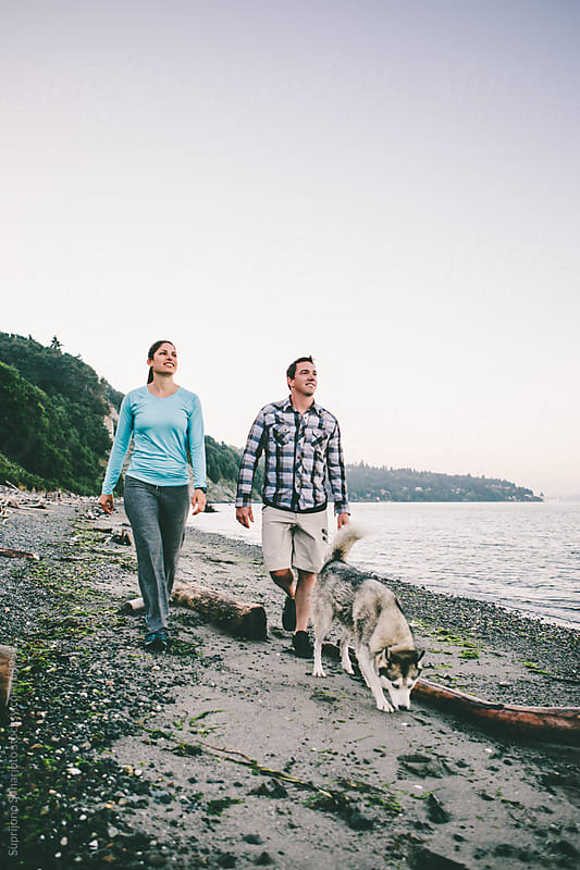 Couple walking with their dog on the beach by Suprijono Suharjoto for Stocksy United