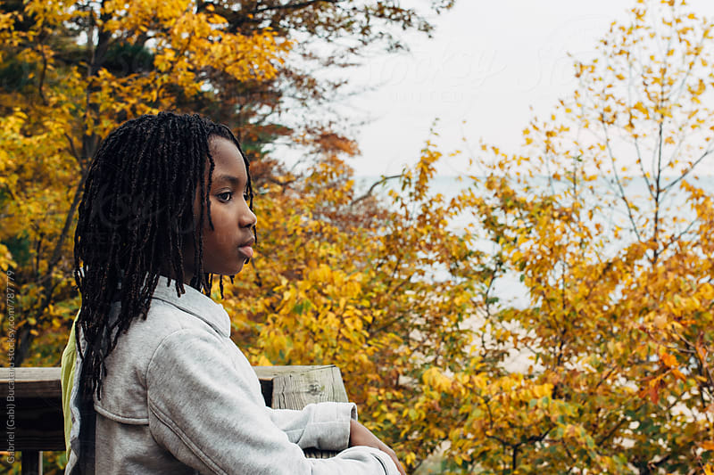 Black girl looking out a scenic view in a fall colored forest by Gabriel (Gabi) Bucataru for Stocksy United
