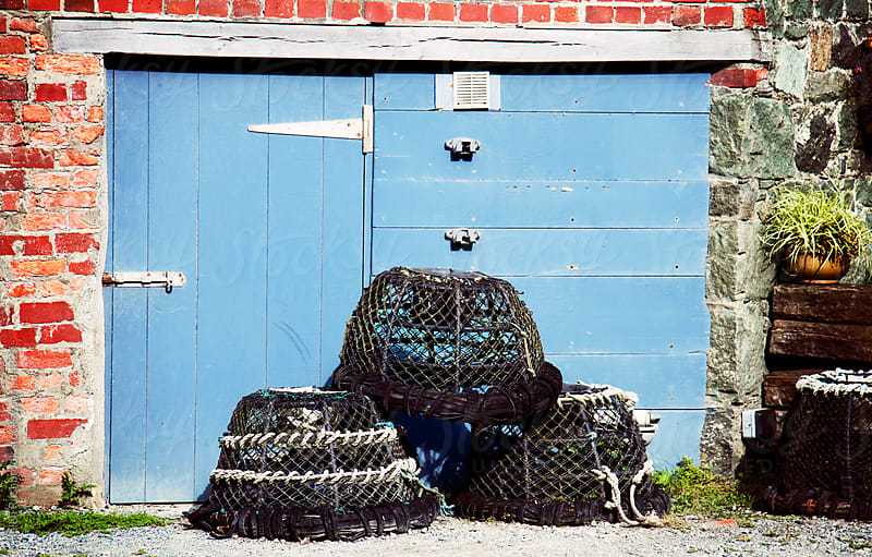 Lobster pots stacked in front of blue doors by Helen Rushbrook for Stocksy United