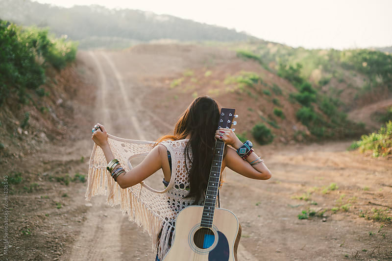 Hippie Woman Carrying her Guitar in the Mountains by Marija Savic for Stocksy United