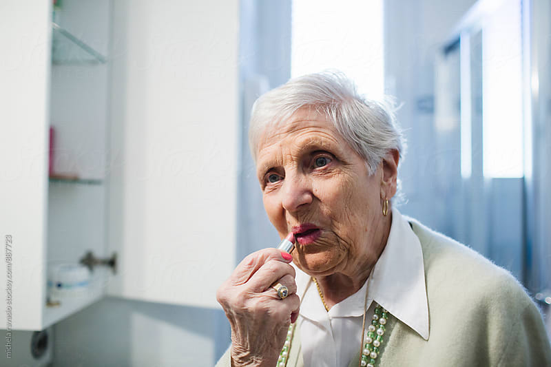 Old lady puts on pink lipstick by michela ravasio for Stocksy United