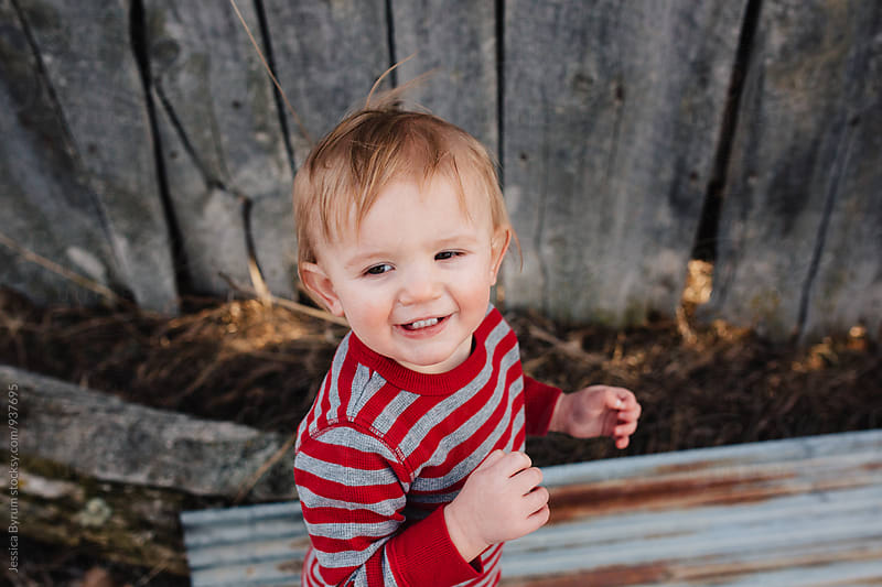 Toddler boy smiling in red striped shirt by Jessica Byrum for Stocksy United