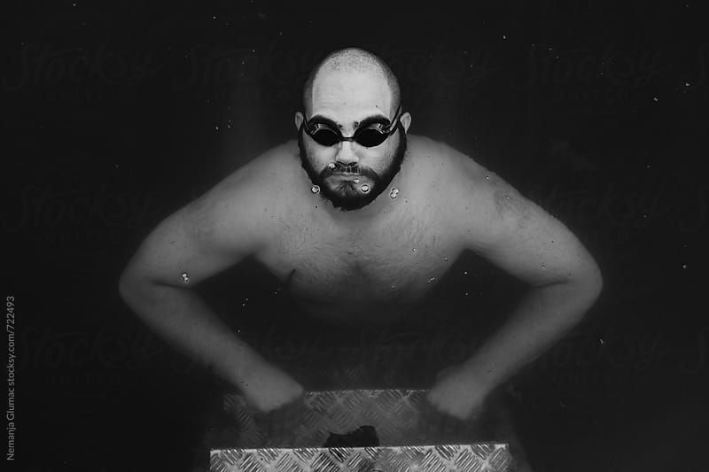 Man With Swimming Goggles Holding Breath Underwater by Nemanja Glumac for Stocksy United