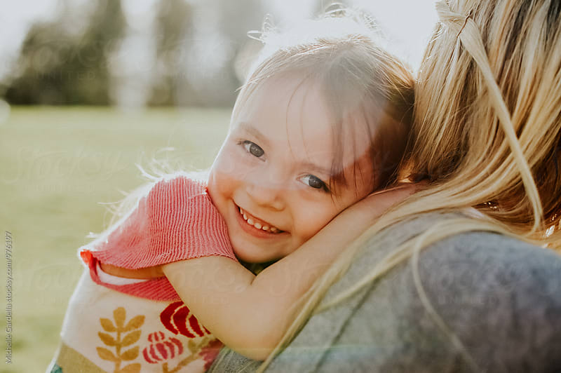 Girl hugging Mom  by Michelle Gardella for Stocksy United