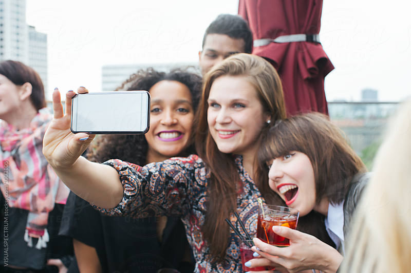 Three Young Women Taking Smartphone Selfie at Rooftop Bar by VISUALSPECTRUM for Stocksy United