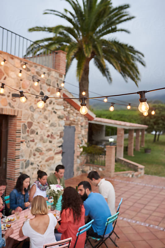 Close-up of decorative illumination garlands above friends having dinner outdoor by Guille Faingold for Stocksy United