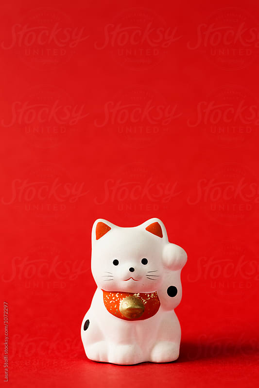 Close up og japanese beckoning cat in porcelain on red background by Laura Stolfi for Stocksy United