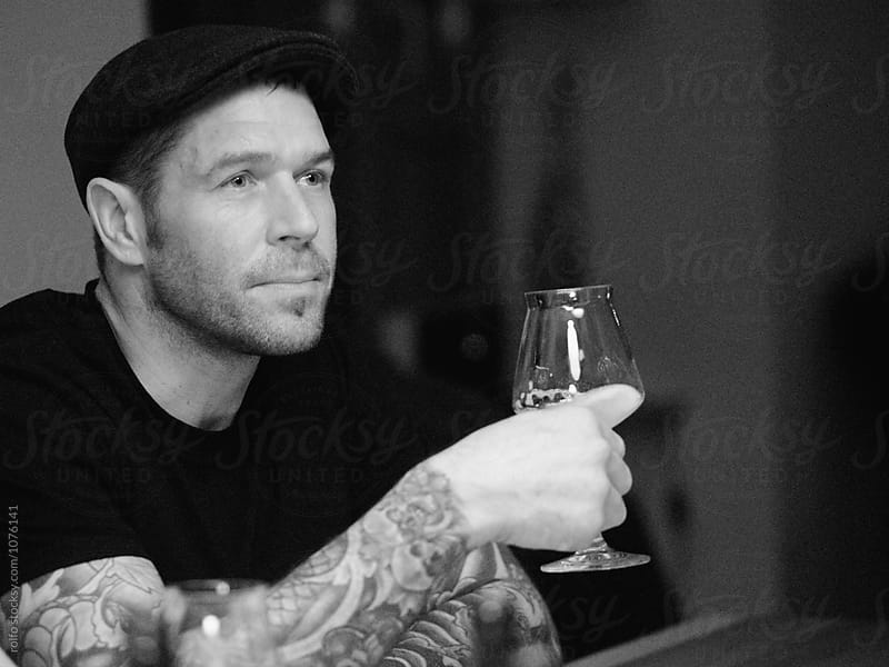 Adult man sitting at table while holding glass of alcohol  by rolfo for Stocksy United