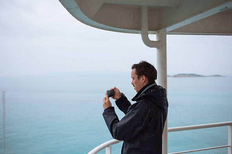 Man taking photos with phone from ferry boat by Marko Milovanović for Stocksy United