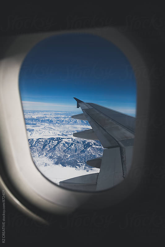 Window seat and snowy mountain range. by Robert Zaleski for Stocksy United