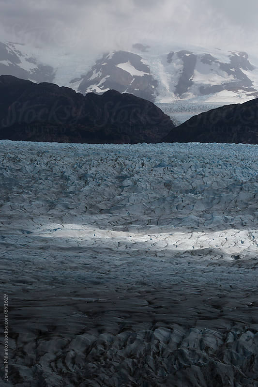 Ice field and mountains under cloudy sky   by Jovana Milanko for Stocksy United
