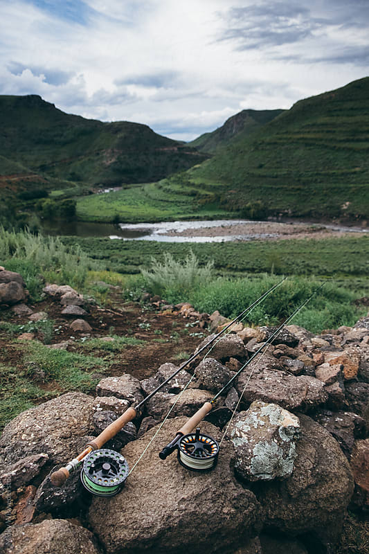 fly fishing rods on a stone wall with a river in the background by Micky Wiswedel for Stocksy United