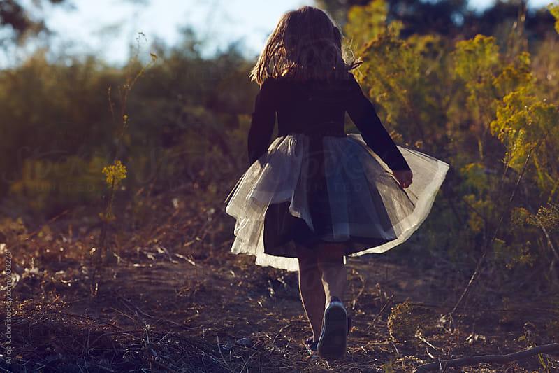 Girl running away in cat costume  by Alicja Colon for Stocksy United