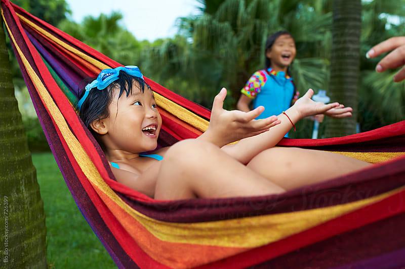 happy little asian girl in hammock by Bo Bo for Stocksy United