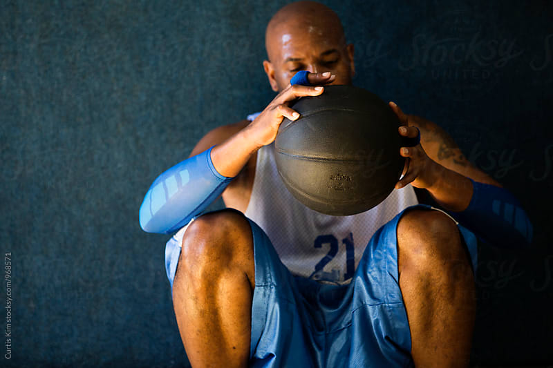 Afro-American basketball player holding ball by Curtis Kim for Stocksy United
