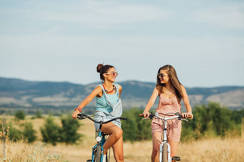 Girls Riding Bicycles Together by Lumina for Stocksy United