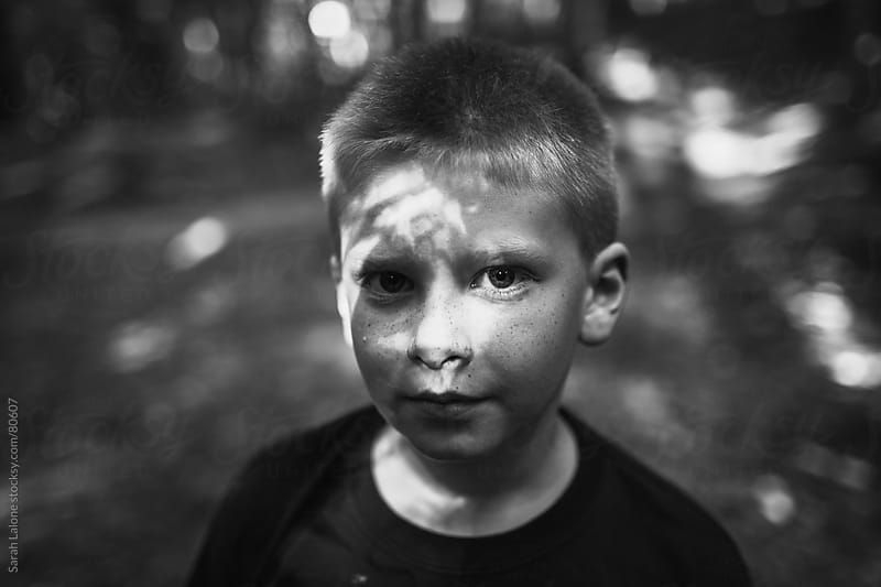 portrait of a serious boy in the woods by Sarah Lalone for Stocksy United