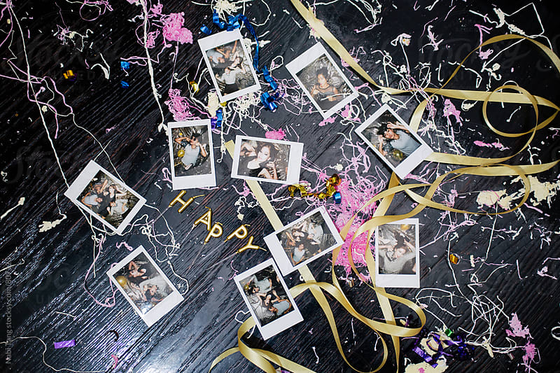 Polaroid photos of people on the dirty floor from the party by Nabi Tang for Stocksy United
