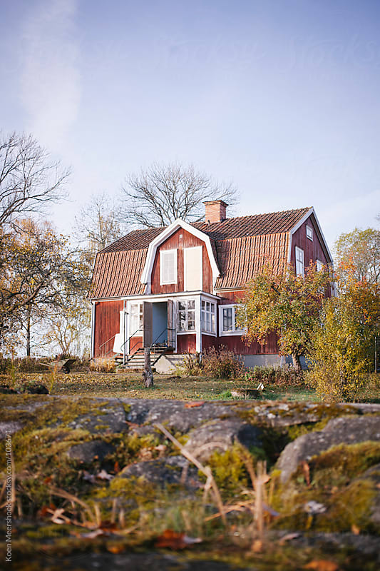 A red house with a large garden. by Koen Meershoek for Stocksy United
