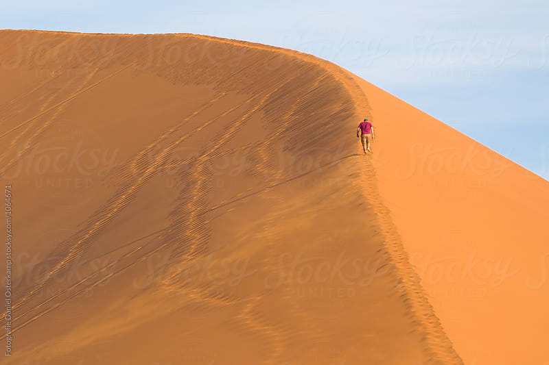Person walking up a sand dune in the namib desert, Namibia, Africa by Fotografie Daniel Osterkamp for Stocksy United