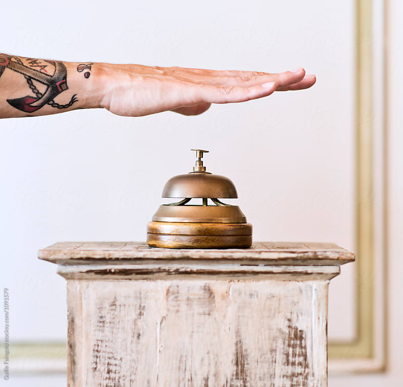 male hand ringing in counter bell by Guille Faingold for Stocksy United