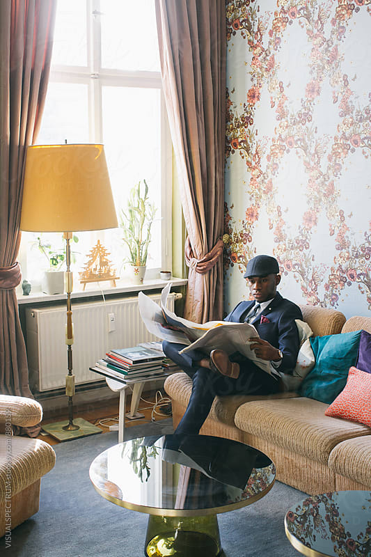 Fashionable Young Black Man Reading Newspaper in Bright Living Room by Julien L. Balmer for Stocksy United