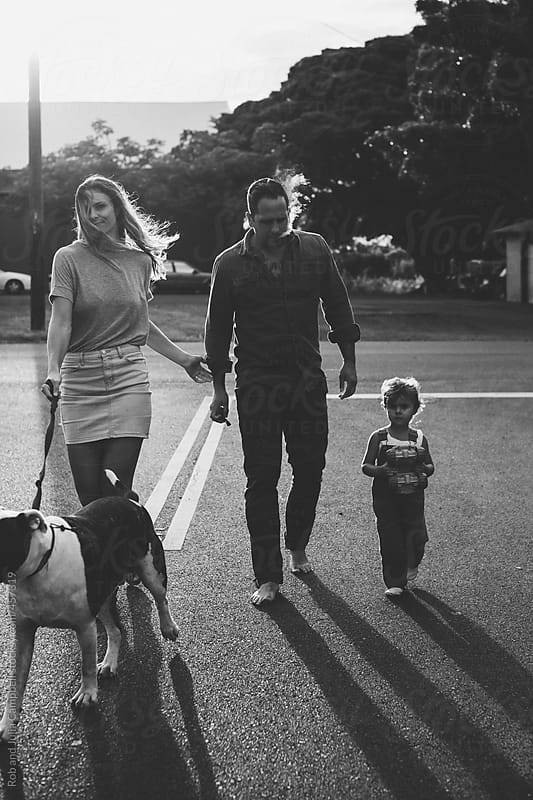 Young, stylish family walking in tropical neighbourhood together with dog by Rob and Julia Campbell for Stocksy United