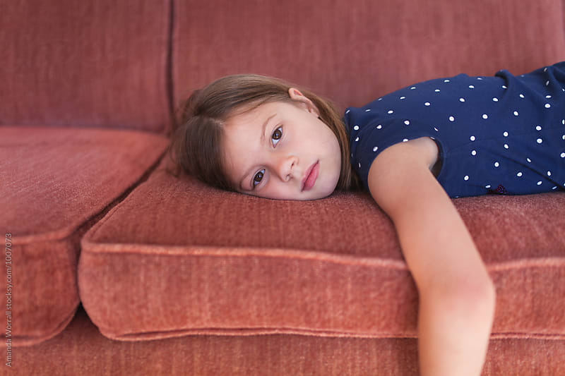 Bored young girl laying on sofa by Amanda Worrall for Stocksy United