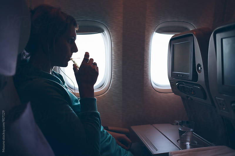 Woman Watching a Movie On an Airplane by Mosuno for Stocksy United