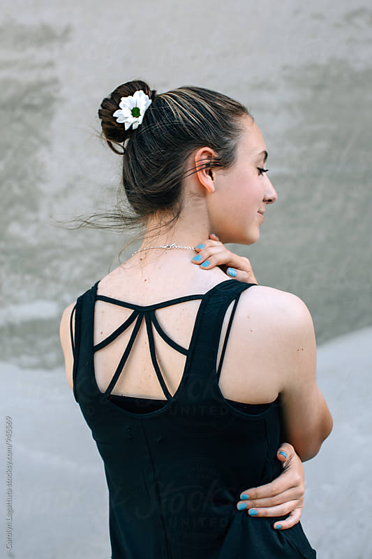 Teenage girl with a flower in her hair  by Carolyn Lagattuta for Stocksy United